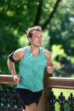 Runner running listening to music app in city park royalty free stock photos