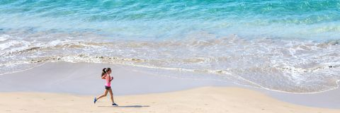 Runner running by the ocean on the beach. Woman runner training cardio running by the ocean on the beach. Morning workout. Panorama horizontal banner crop for royalty free stock photography