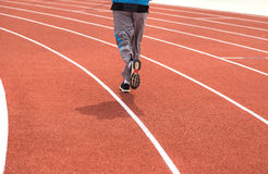 Runner is running on the running track. Runner is running on the running track in stadium Royalty Free Stock Photos
