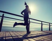 Runner running on seaside boardwalk during sunrise. Sporty female runner running on seaside boardwalk during sunrise Royalty Free Stock Images