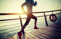Runner running on seaside boardwalk during sunrise Royalty Free Stock Images