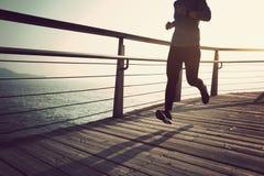 Runner running on seaside boardwalk during sunrise. Sporty female runner running on seaside boardwalk during sunrise Royalty Free Stock Photos