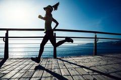 Runner running on seaside boardwalk during sunrise. Sporty female runner running on seaside boardwalk during sunrise Stock Images