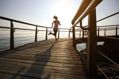 Runner running on seaside boardwalk during sunrise. Sporty fitness female runner running on seaside boardwalk during sunrise Royalty Free Stock Photos