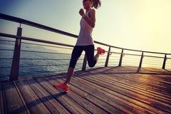 Runner running on seaside boardwalk during sunrise. Sporty fitness female runner running on seaside boardwalk during sunrise Stock Photos