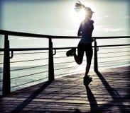 Runner running on seaside boardwalk during sunrise. Sporty fitness female runner running on seaside boardwalk during sunrise Stock Photo