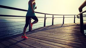 Runner running on seaside boardwalk during sunrise. Sporty fitness female runner running on seaside boardwalk during sunrise Stock Photography