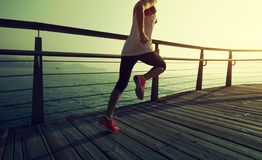 Runner running on seaside boardwalk during sunrise. Sporty fitness female runner running on seaside boardwalk during sunrise Stock Images