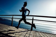 Runner running on seaside boardwalk during sunrise. Sporty fitness female runner running on seaside boardwalk during sunrise Royalty Free Stock Images