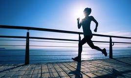 Runner running on seaside boardwalk during sunrise. Sporty fitness female runner running on seaside boardwalk during sunrise Stock Image