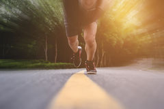 Runner running straight to camera on the road, with speed motion on border, selective focus on shoes Royalty Free Stock Photography