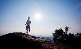 Runner running on sunrise mountain top edge Royalty Free Stock Images