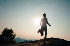 Runner running on sunrise mountain top edge Stock Photos