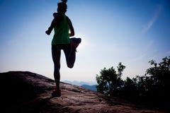 Runner running on sunrise mountain top edge Stock Photo