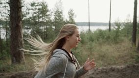 A runner runs through a pine forest. A blonde in a gray sports suit runs in the forest. stock video