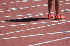 Runner's legs and shadow on track. A female sprinter's strong legs and shadow on a track. Taken at an invitational track meet in Arizona 2016 Stock Photos
