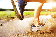 Runner's sneakers splashing in mud puddle Royalty Free Stock Images