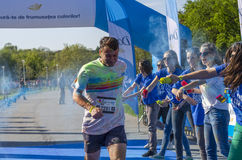 Runner showered with blue powder. Cheering girls throwing blue powder at male runner at one station during the Color Run event on April 26 in Bucharest, Romania Royalty Free Stock Images