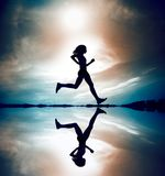 Runner Silhouetted Reflection. Female runner silhouette is mirrored below with a soft pastel sunset sky as backdrop stock photography