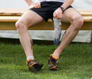 Runner siting after foot race. A runner siting after foot race with socks in his hand Royalty Free Stock Photos