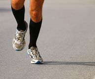 Runner with sneakers during the Marathon on paved road Royalty Free Stock Photography