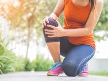 Runner sport knee injury. Woman in pain while running. In the garden royalty free stock photo