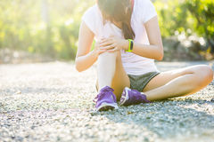 Runner sport knee injury. Woman in pain. While running in park Stock Photo