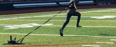 Runner sprinting pulling a weght sled. A runner is sprinting, bounding, down a green turf field pulling a led with 50 lbs of weight on it Stock Photo