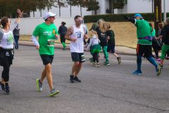 Runner in St Patricks Day Parade with woman excitedly waving at man running the other way who is waving back Tulsa Oklahoma USA 3 royalty free stock image