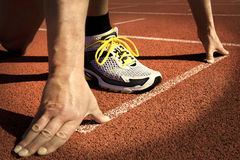 Runner stadium start position. Runner in a stadium is in start position with hands on the line Stock Image