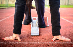 Runner in a stadium is in start position with hands on the line.  Stock Images