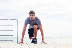 Runner standing in start position outdoors. Portrait of a young male runner standing in start position outdoors Stock Image