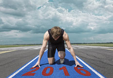 Runner start position runway. Male version of airport runway starter. Runner in start position kneels with lowered head on a red tartan surface, ready to take of Stock Image