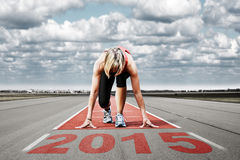 Runner start runway 2015. Female sprinter waiting for the start on an airport runway.In the foreground perspective view of the date 2015 royalty free stock photos
