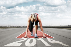 Runner start runway 2014. Female sprinter waiting for the start on an airport runway.In the foreground perspective view of  letters 2014 Stock Images