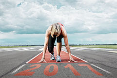 Runner start runway 2017. Female runner waits for the 2017 start on an airport runway. In the foreground perspective view of the  date 2017 Royalty Free Stock Photos