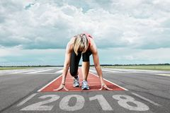 Runner start runway 2017. Female runner waits for his start at an airport runway. In the foreground the painted date 2018 Royalty Free Stock Photos