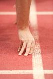 Runner at the starting line. Close-up of the hands of runner lined up at the starting line Royalty Free Stock Images
