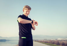 Runner starts his modern stopwatch before jogging Royalty Free Stock Photo