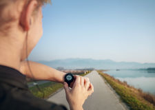 Runner starts his modern stopwatch before running Royalty Free Stock Photos