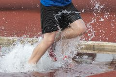 Runner in a steeple chase water bake on a running track royalty free stock image