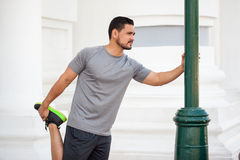 Runner stretching in the city Stock Photo