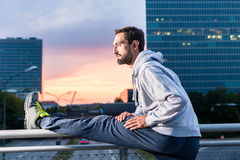 Runner stretching in front of office building at sunset Royalty Free Stock Photography