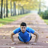 Runner Stretching out. Male runner stretching after running in cold fall weather wearing warm sporty running clothing. Handsome male fitness sport model outdoors Stock Photography