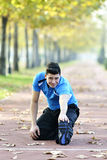 Runner Stretching out. Male runner stretching after running in cold fall weather wearing warm sporty running clothing. Handsome male fitness sport model outdoors Royalty Free Stock Photography