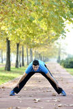 Runner Stretching out. Male runner stretching after running in cold fall weather wearing warm sporty running clothing. Handsome male fitness sport model outdoors Stock Photos