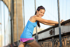 Runner stretching and running, Brooklyn, New York. Runner stretching after running on Brooklyn Bridge, New York City, Manhattan. Fit woman fitness model portrait stock images