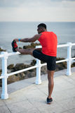 Runner stretching for warming up before running. Male fit runner stretching towards the sea for warming up before running. Black athlete exercising Royalty Free Stock Photography
