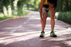 Runner suffering with pain on sports running knee injury. Female runner suffering with pain on sports running knee injury royalty free stock images