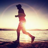 Runner in Sun rays on beach. Sportsman in baseball cap, jogging during the sunrise above sea Royalty Free Stock Images